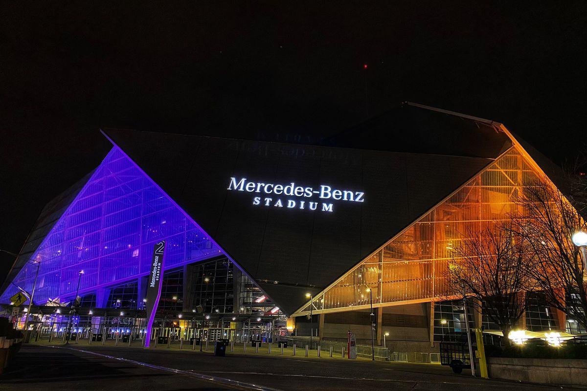 The Mercedes-Benz Stadium illuminated purple and gold.