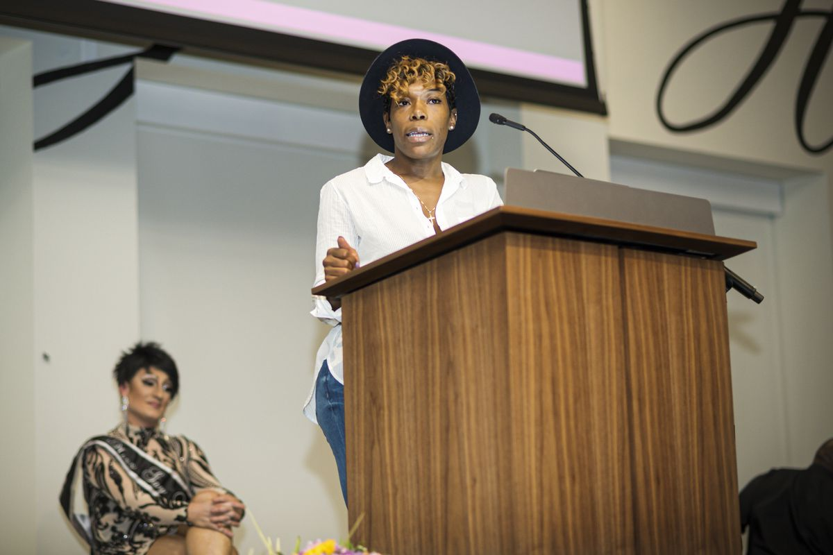 Eisha Love stands onstage behind a podium and speaks to an audience.