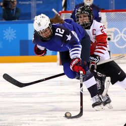 Kelly Pannek #12 of the United States battles for the puck against Marie-Philip Poulin #29 of Canada in the second period.