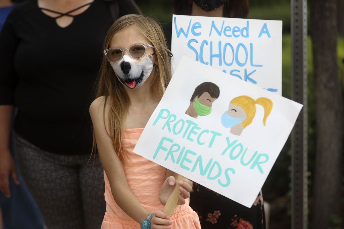 Torah Neil, 10, holds a sign in support of school mask mandates in Salt Lake City.