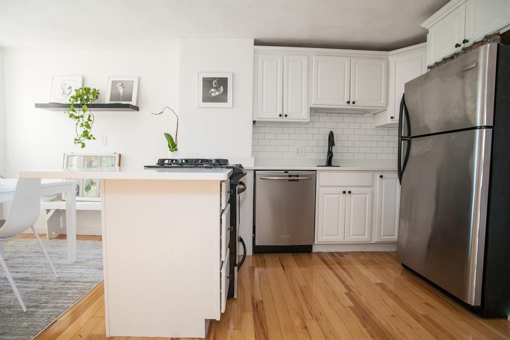 A small kitchen with a U-shaped counter and a fridge.