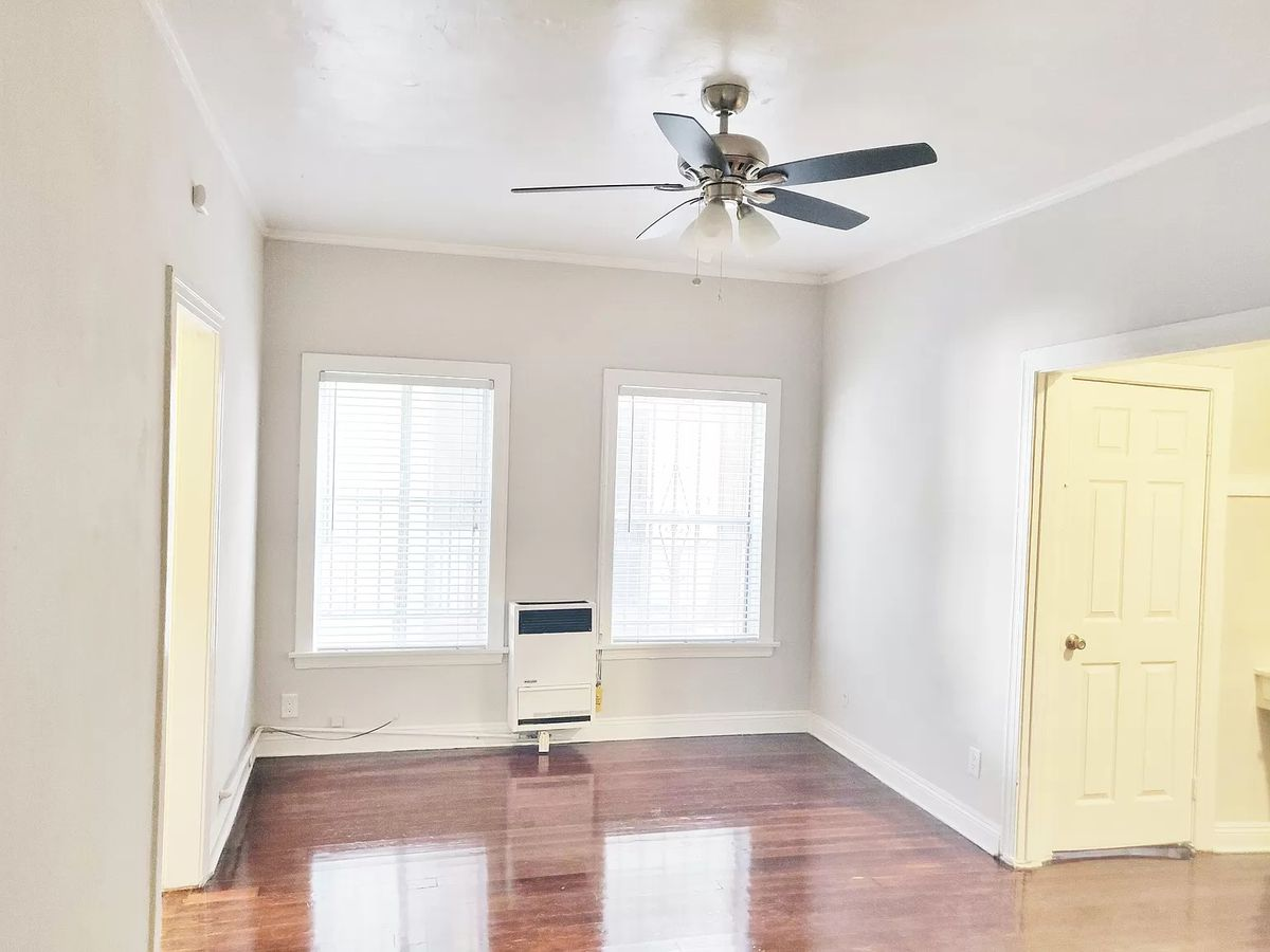 Living room with two vertical windows parallel to each other, and a ceiling fan.