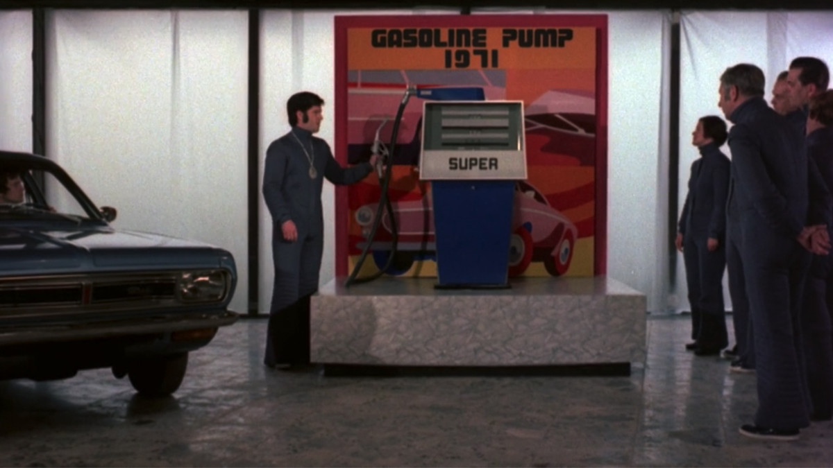 A group of men in a 20th-century museum in ZPG try out a 1970s-style gas pump