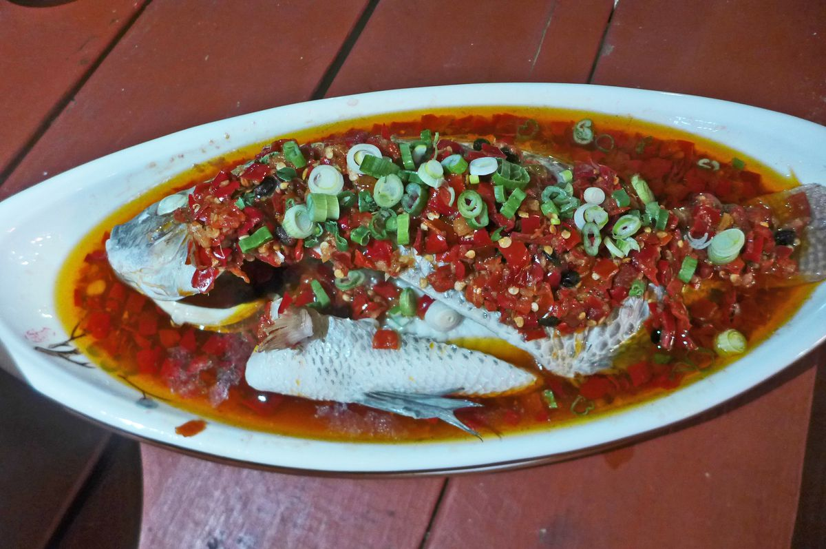 A whole fish swimming in red oil, eyeballs opaque.