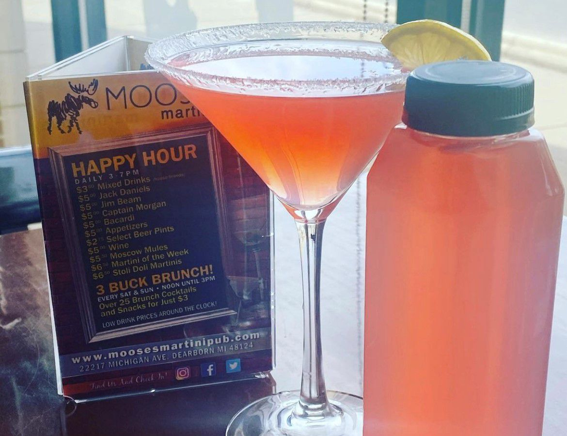 A light pink cocktail in a martini glass next to a bottle of the same pink cocktail on a table