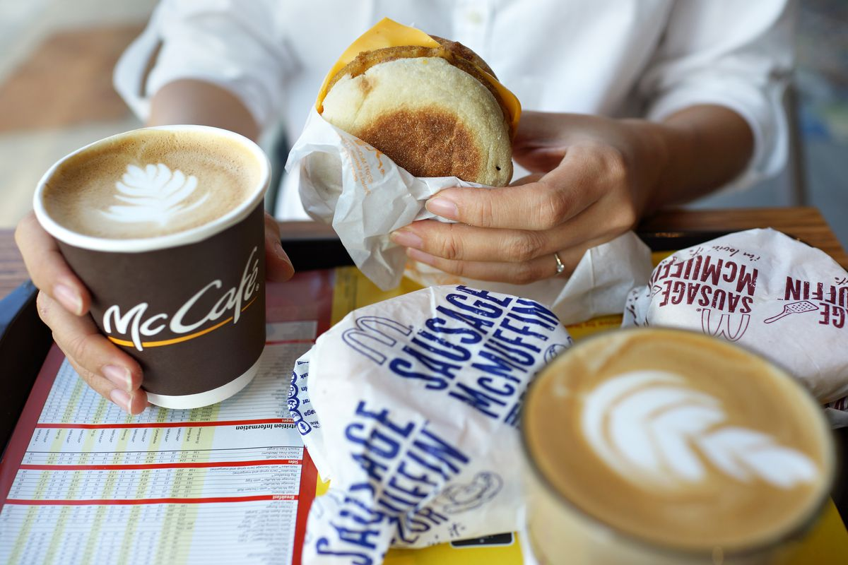 Hands holding a McMuffin over a tray of McDonald's breakfast and coffee.