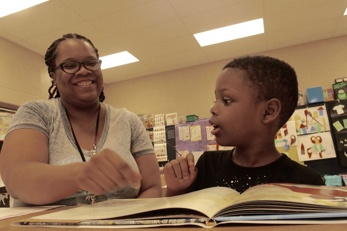Teacher Dorian Lloyd helps rising first-grader Nykari McNeal sound out words during a state-funded reading camp at Cornerstone Prep Denver, a Memphis charter school in the Achievement School District.