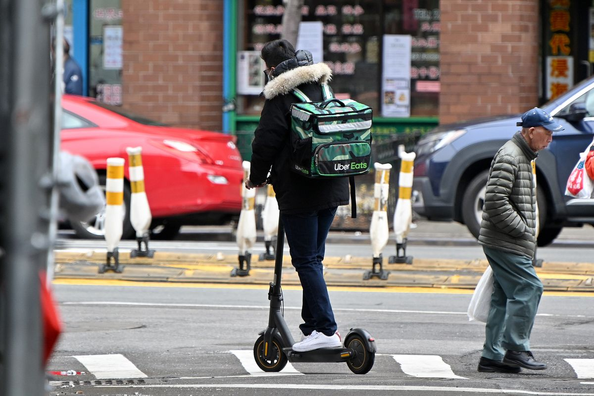 An Uber Eats delivery worker is seen riding an electric scooter in Manhattan's Chinatown on March 19, 2020 in New York City.