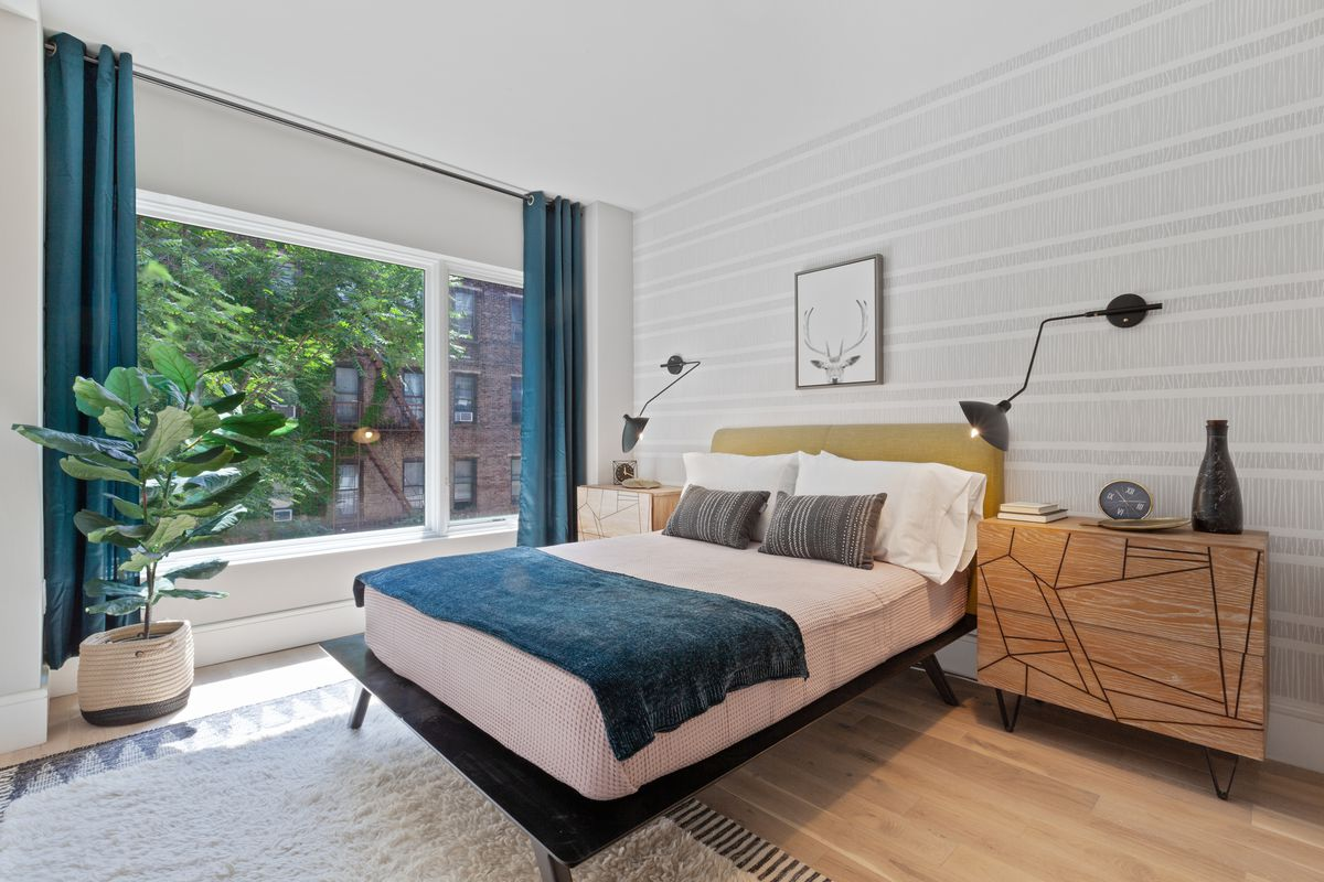 A bedroom with a floor-to-ceiling window, hardwood floors, a planter, and a medium-sized bed.