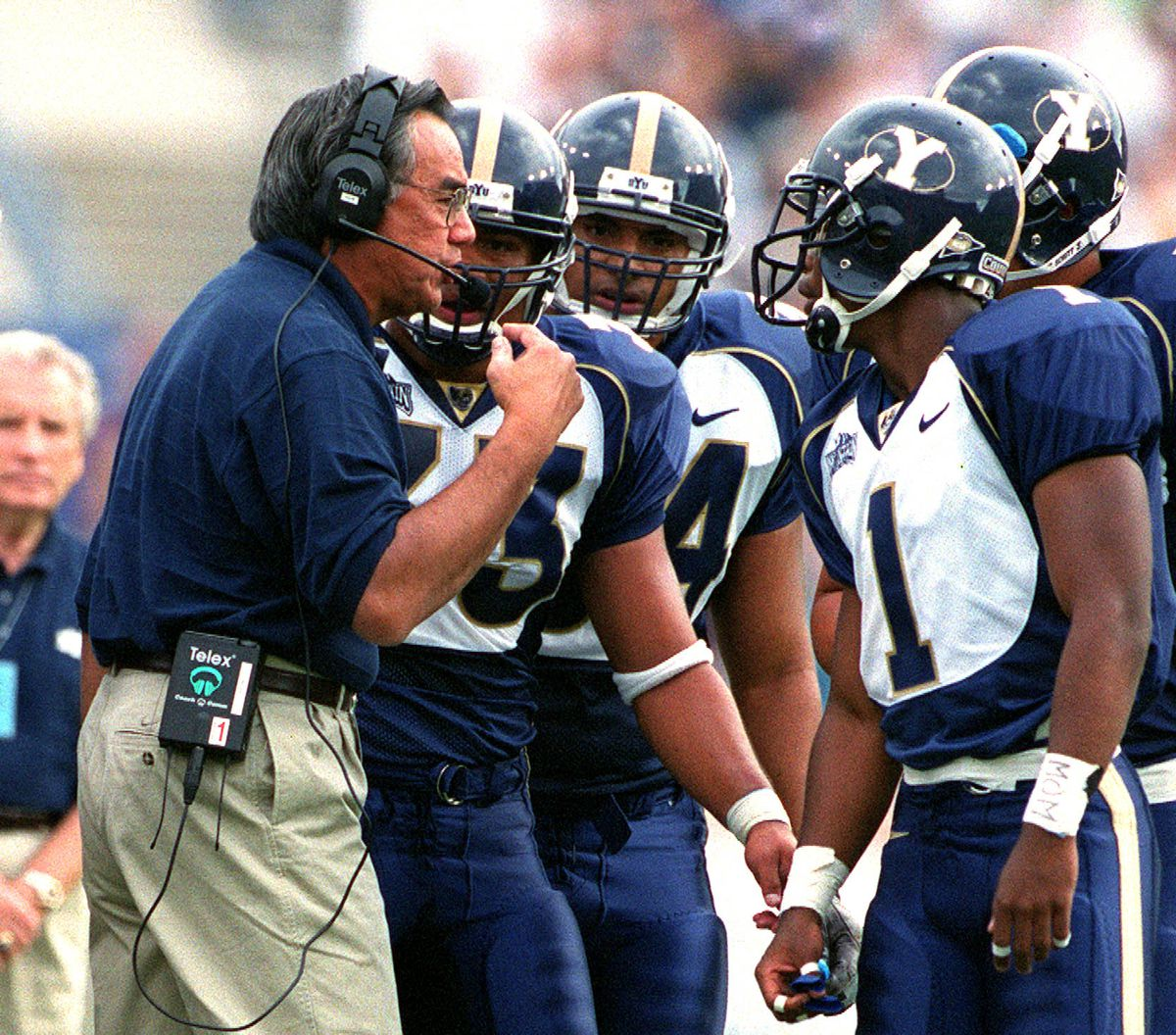 BYU offensive coordinator Norm Chow, left, instructs players during a timeout during their game against Washington on Sept. 9, 1999.