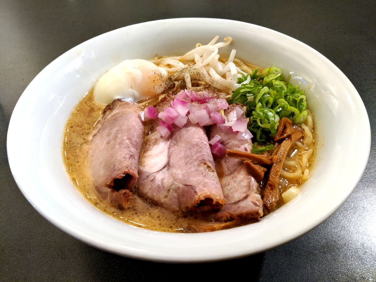 A white bowl filled with slices of pork, chopped onions, and various toppings