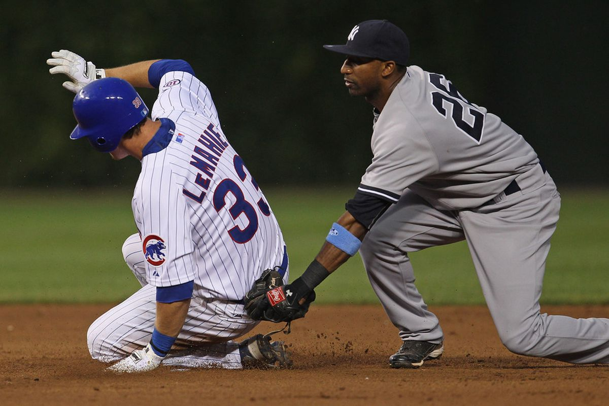 D.J. LeMahieu of the Chicago Cubs slides safely into 2nd base with a double ahead of the tag by Robinson Cano of the New York Yankees at Wrigley Field on June 19, 2011 in Chicago, Illinois. (Photo by Jonathan Daniel/Getty Images)