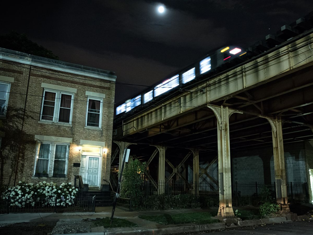 A night time view under an elevated train tracks under a moonlit sky.