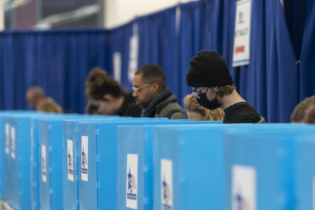A voter wearing a face masks votes at a polling supersite in the Loop