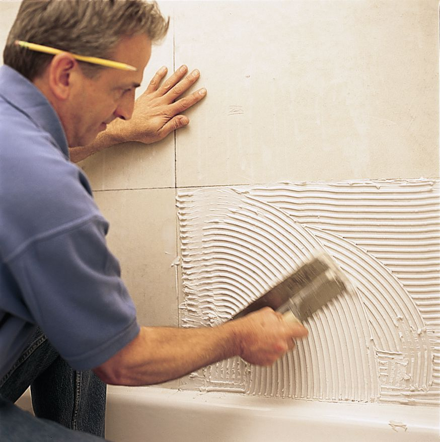 Man Uses Trowel To Spread on Tile Mastic For Tile Surround
