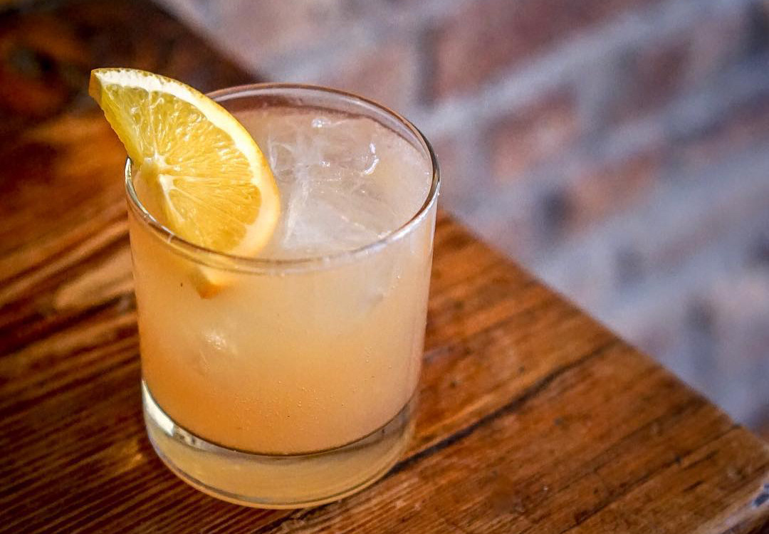 A drink in a glass tumbler with a wedge of orange.