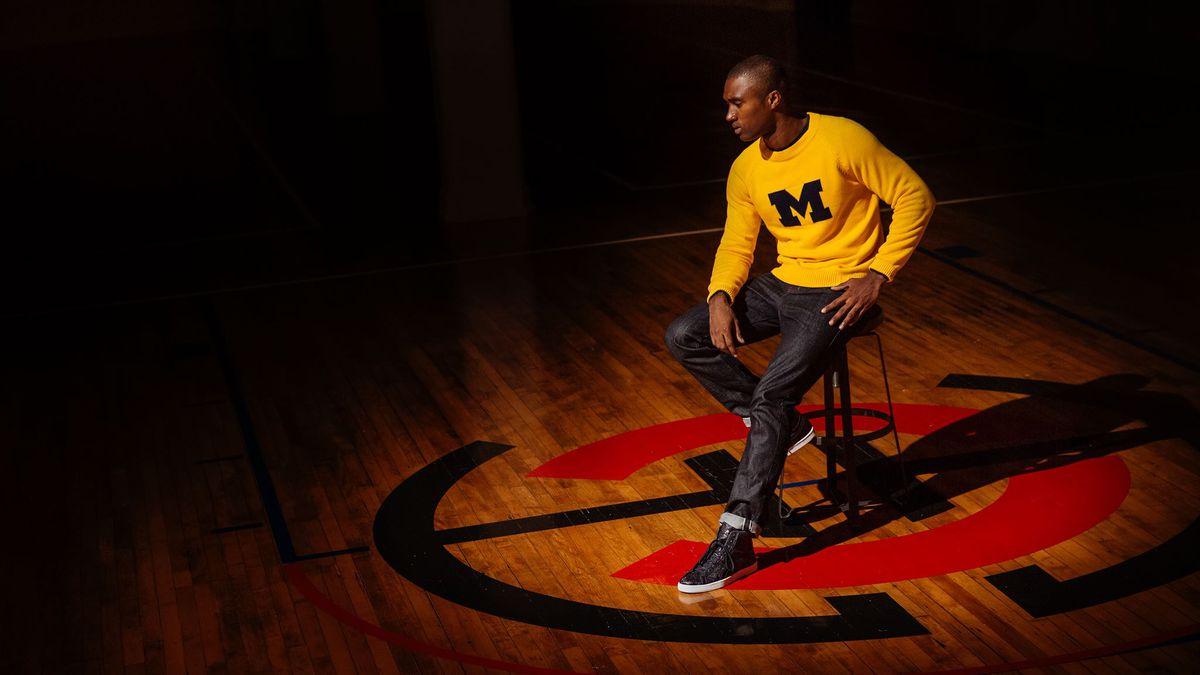 A man wearing a Michigan college sweatshirt, sitting in a basketball court