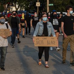 A group of activists march down 60th Street in Kenosha, during a protest over the shooting of Jacob Blake, Tuesday, Aug. 25, 2020.