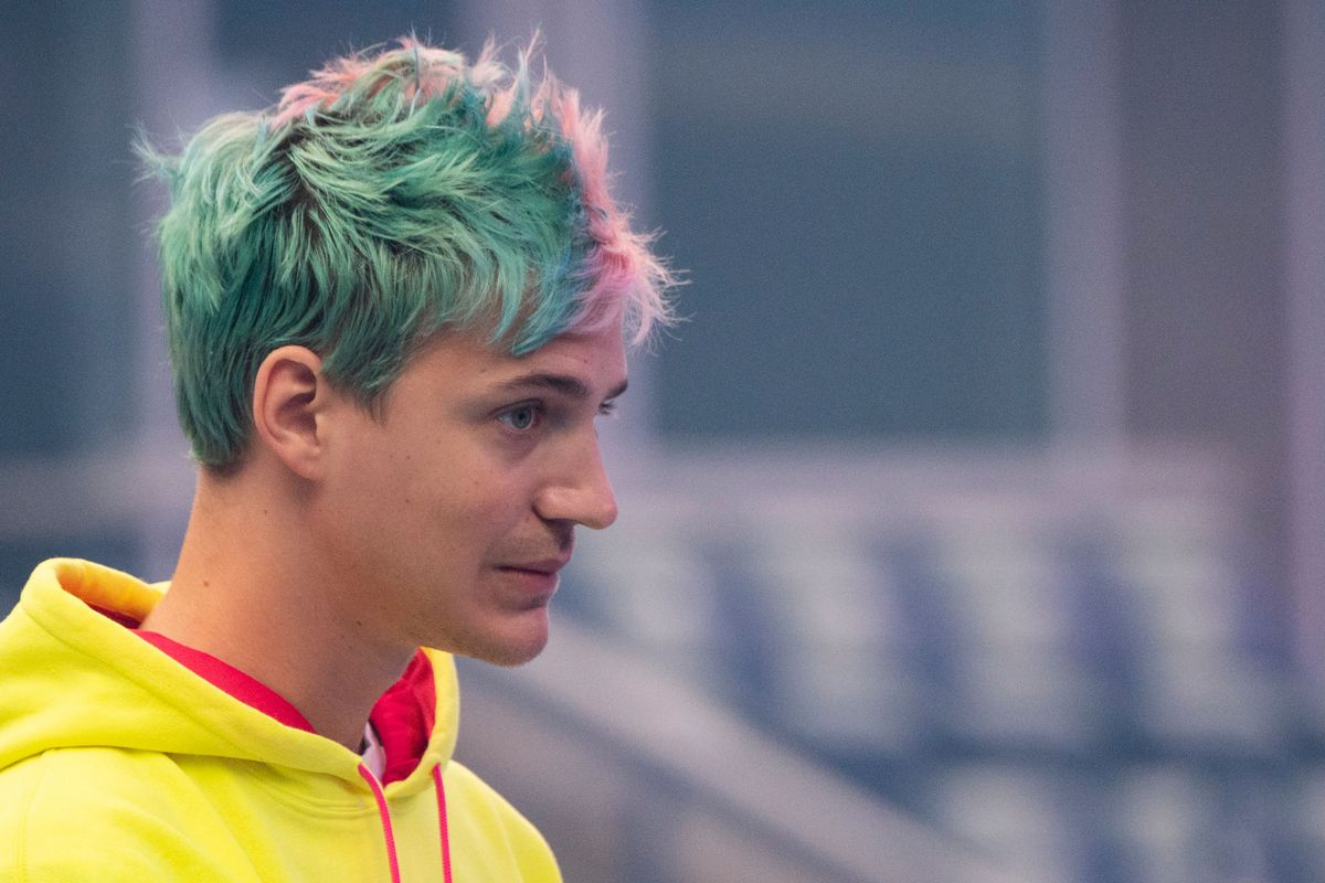Tyler Ninja Blevins in a yellow hoodie, speaking to a large crowd at the 2019 Fortnite World Cup Finals
