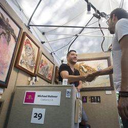 Michael Rohner shakes hands with a fellow artist from Oakland, California, in his booth on the first day of the Utah Arts Festival in Salt Lake City on Thursday, June 22, 2017.