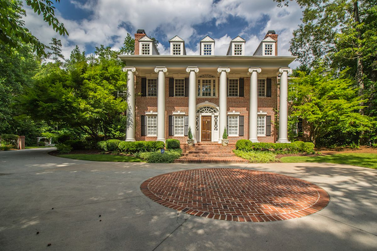 Driveway in front of two-story brick home with columns.