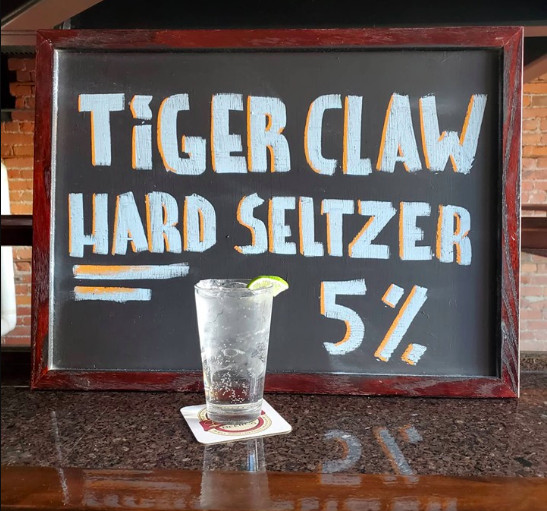 A pint glass filled with clear, hard seltzer with a lime wedge garnish sits in front of a chalkboard reading Tiger Claw Hard Seltzer 5%.