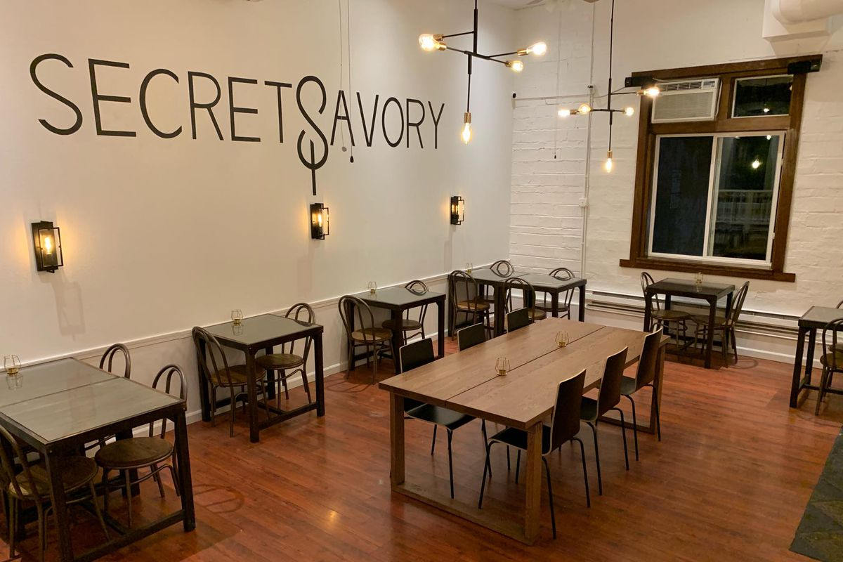 A view of Secret Savory restaurant's interior, with the name written on one wall, plus Edison bulbs and dark wood furniture in the dining room.