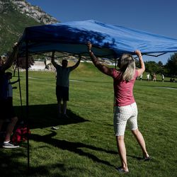 John and Brooke Rodgerson and their children, Payton, left, Cameron, second from left, and Carter, not pictured, set up a canopy and chairs at Rock Canyon Park in Provo on Saturday, July 4, 2020.