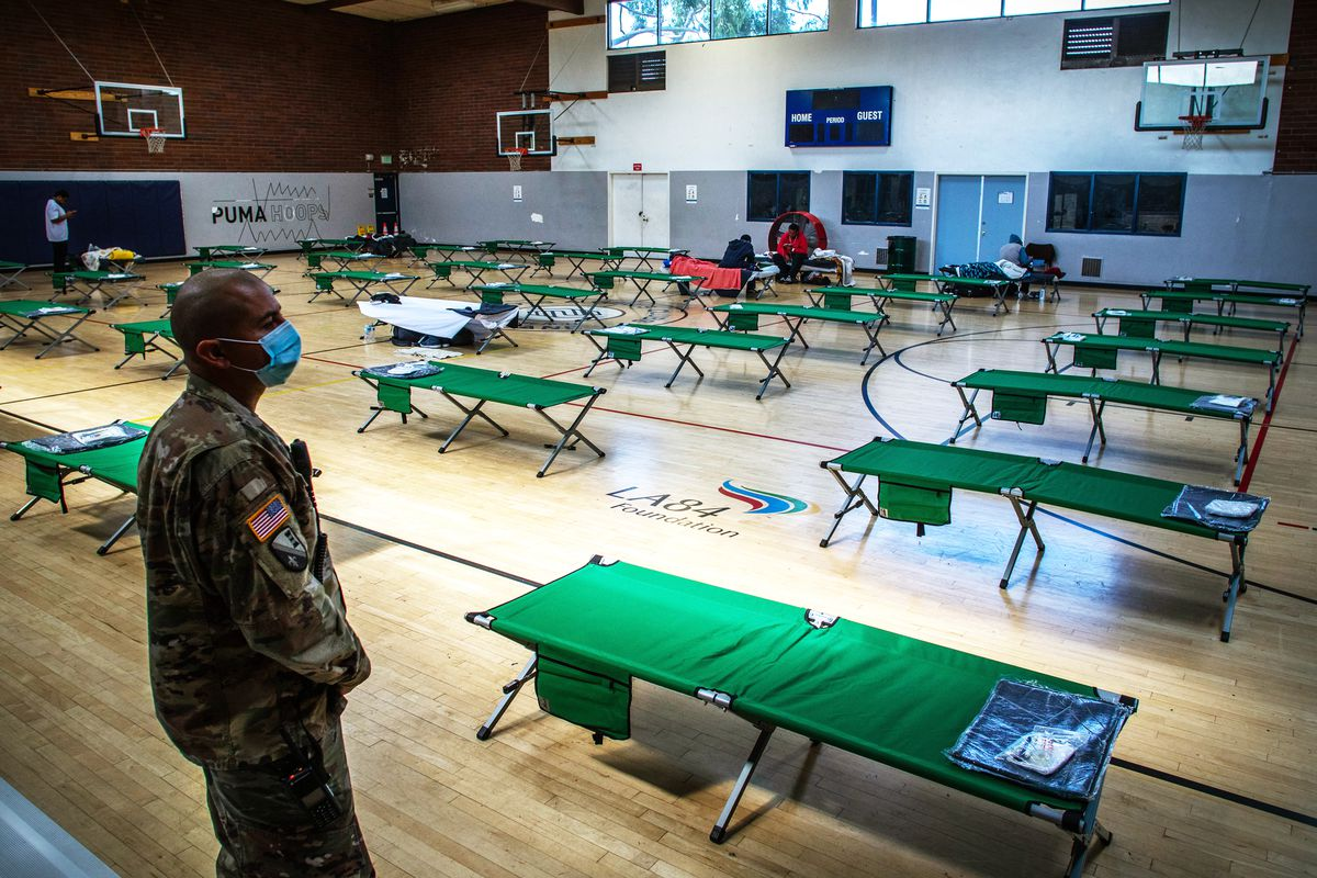 A person in Army camouflage gear looks at a gymnasium floor covered in folding cots opened and placed 10 feet apart from one another.