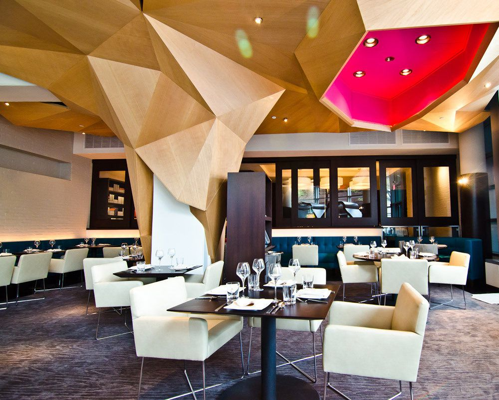 A view of Rasika's private dining room, with seating in the foreground and dropping wall hangings in wood and fuschia.