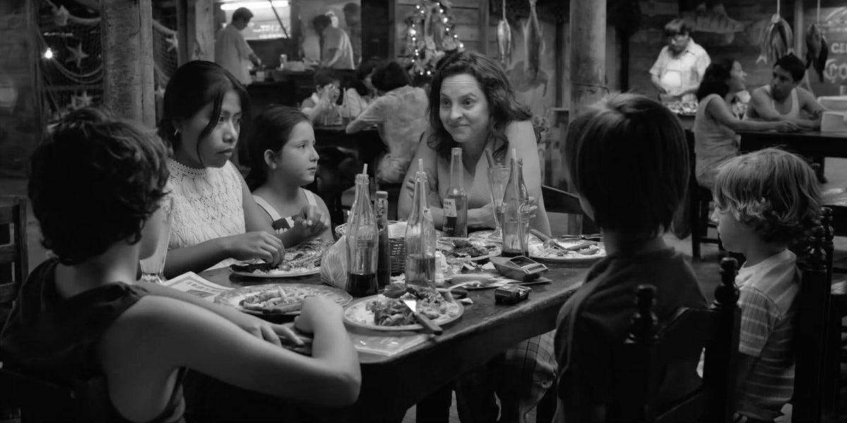The family gathers around a table in Roma.