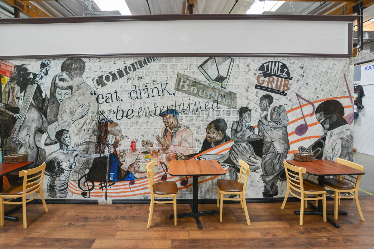 A jazz mural with assorted tables inside of a warehouse-like space.