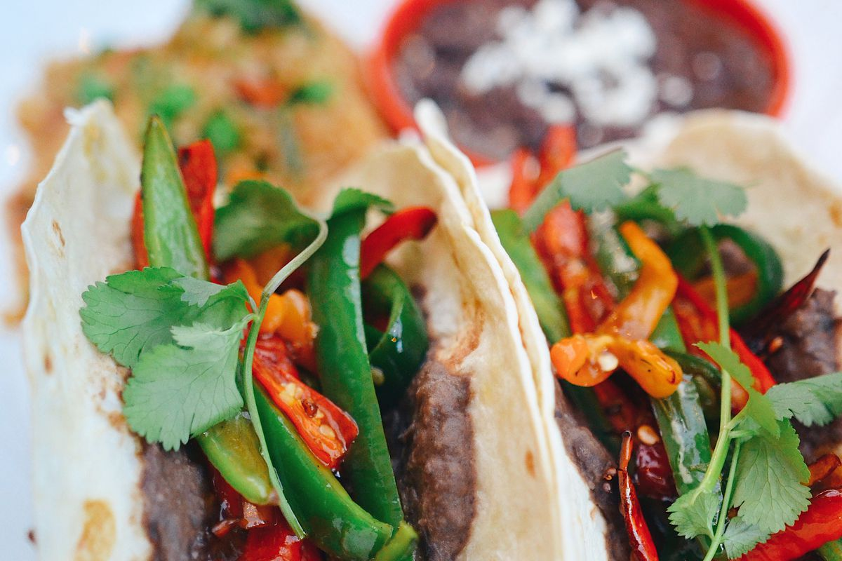 a plate of beef tacos covered in red and green peppers