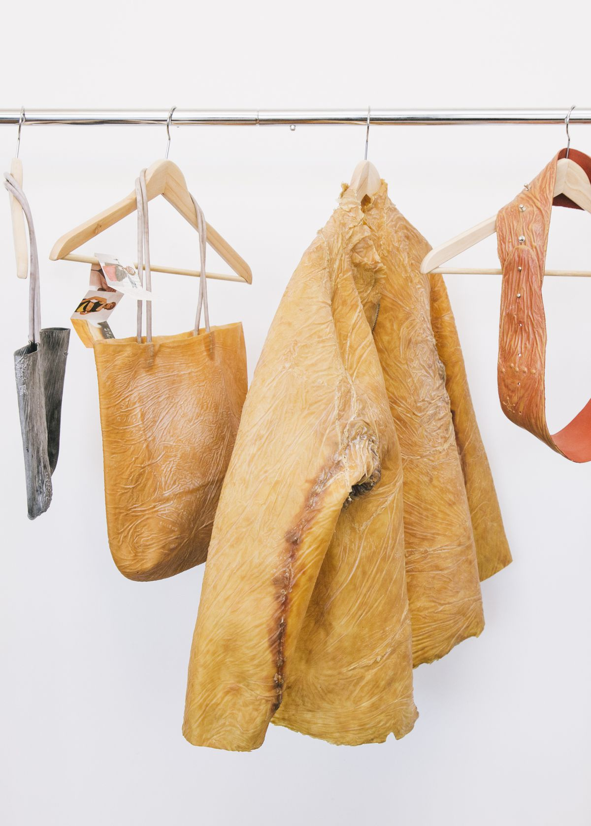 A coat, a bag, and a belt hanging on hangers. The materials look like flesh.