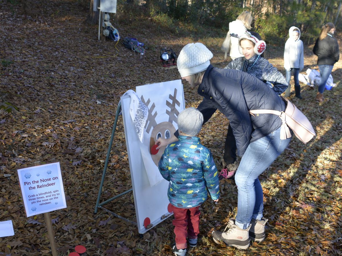 A child and an adult look at a painting of a reindeer in an outdoor area near trees.