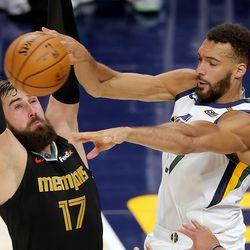 Utah Jazz center Rudy Gobert (27) passes the ball around Memphis Grizzlies center Jonas Valanciunas (17) as the Utah Jazz and the Memphis Grizzlies play in game one of their NBA playoff series at Vivint Arena in Salt Lake City on Sunday, May 23, 2021.