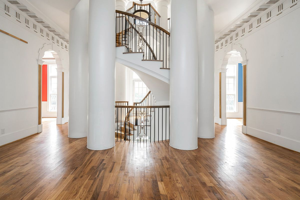A room with several huge white columns around a spiral staircase.