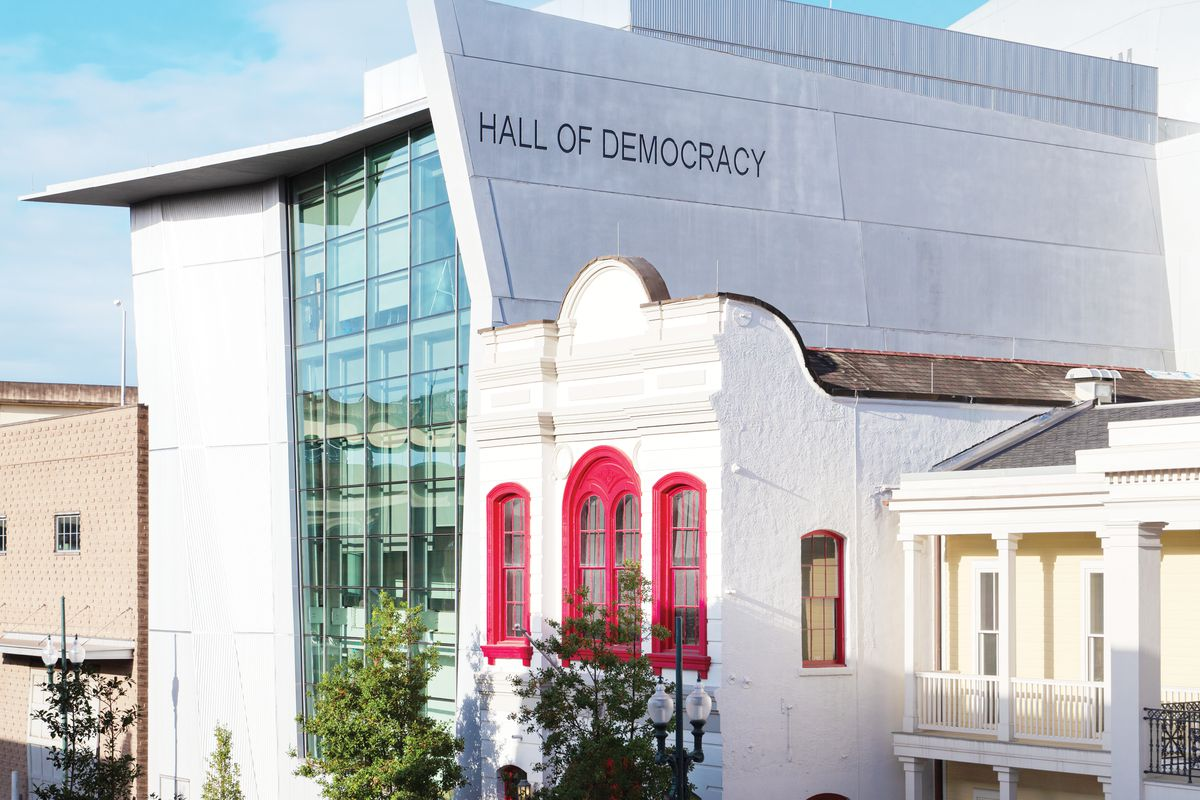 """The words """"HALL OF DEMOCRACY"""" are stamped across a concrete building that features a wall of glass."""
