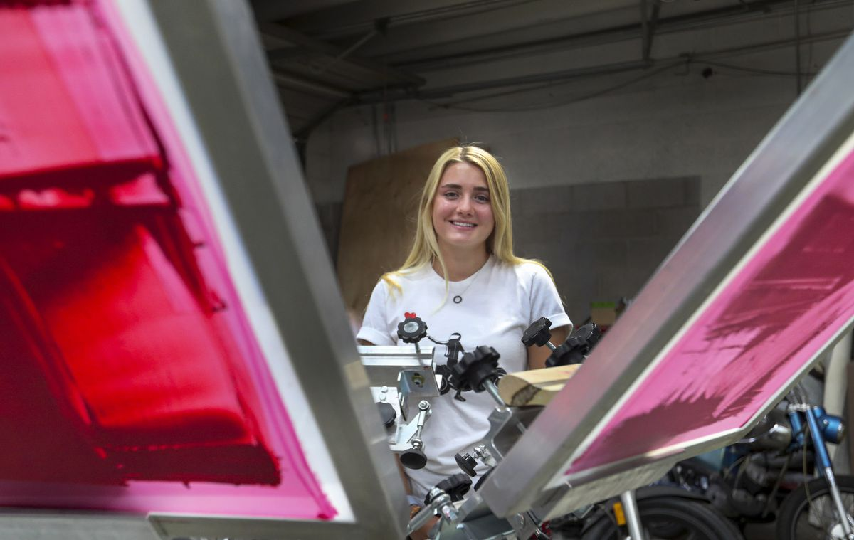 University of Utah freshman Stephanie Burnham poses for a photo with a screen printing machine at her family's business in Salt Lake City on Tuesday, Oct. 6, 2020. Burnham lives on campus in the Lassonde Entrepreneur Institute Studio building and is a member of a new cohort there that is made up of students who founded companies in high school or earlier.