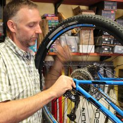 Springdale business owner Fred Pagles repairs a bicycle in his shop. Pagles said a possible government shutdown could reduce his business at Zion Cycles between 50 percent and 70 percent.