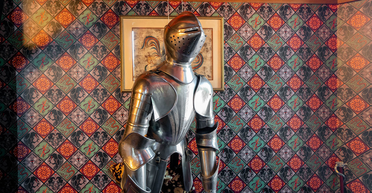 A suit of armor set against a decorative wall.