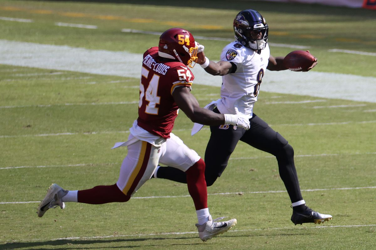 Baltimore Ravens quarterback Lamar Jackson (8) runs with the ball as Washington Football Team outside linebacker Kevin Pierre-Louis (54) chases in the third quarter at FedExField.