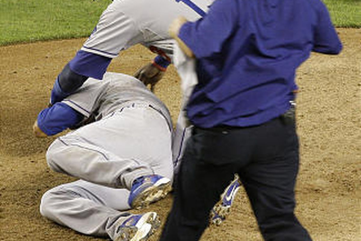 Los Angeles Dodgers' Hiroki Kuroda, left, of Japan, is attended by teammate Orlando Hudson, center, as assistant athletic trainer Todd Tomczyk, right, runs out to check Kuroda after he was hit in the head on a line drive.