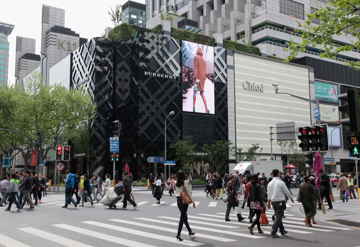 Pedestrians walk by the Burberry store in Shanghai