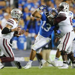 Mississippi State Bulldogs quarterback Nick Fitzgerald (7) looks for an open receiver as Brigham Young Cougars linebacker Francis Bernard (13) works to get past Mississippi State Bulldogs offensive lineman Jamaal Clayborn (60) as BYU and Mississippi State play in Provo at LaVell Edwards Stadium on Friday, Oct. 14, 2016.
