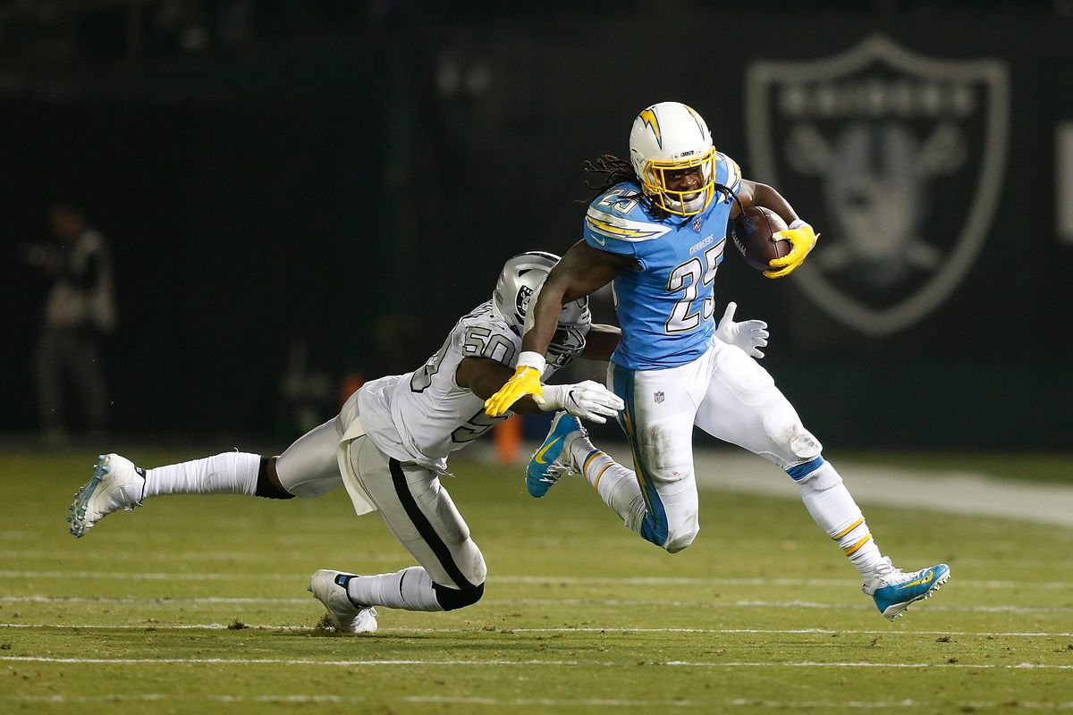 Melvin Gordon of the Los Angeles Chargers evades a tackle by Nicholas Morrow of the Oakland Raiders in the third quarter at RingCentral Coliseum on November 07, 2019 in Oakland, California.