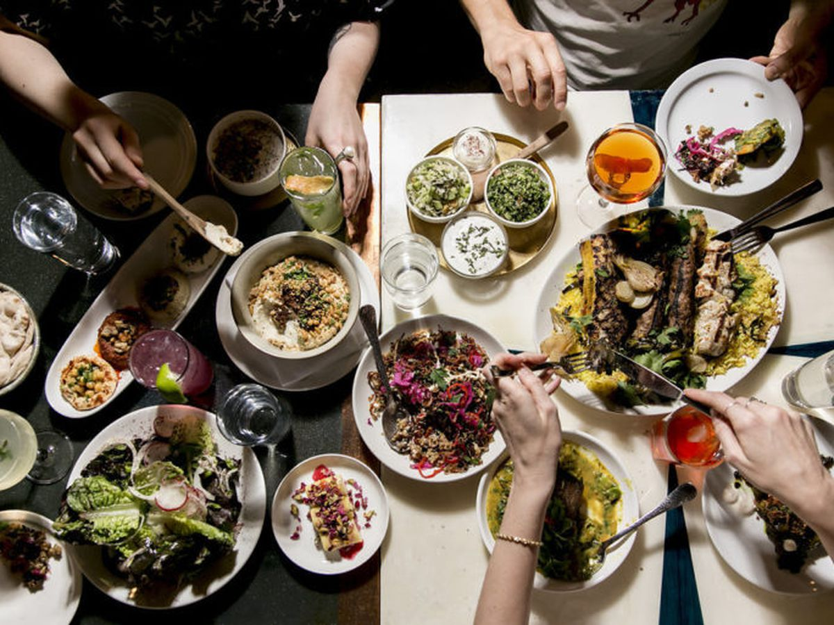 A top-down view of a full meal at Mamnoon, with multiple plates of vegetables, meat, and sides.