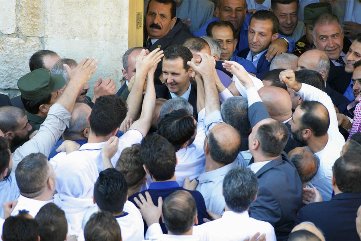 """FILE """""""" In this photo released by the Syrian official news agency SANA, Syrian President Bashar Assad, center, greeting Syrians following the prayers of the first day of Eid al-Fitr, that marks the end of the Muslim holy month of Ramadan, at the Nouri Mos"""
