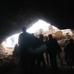 Members of a tour group inside Jukebox Cave peer out into the sunlight.