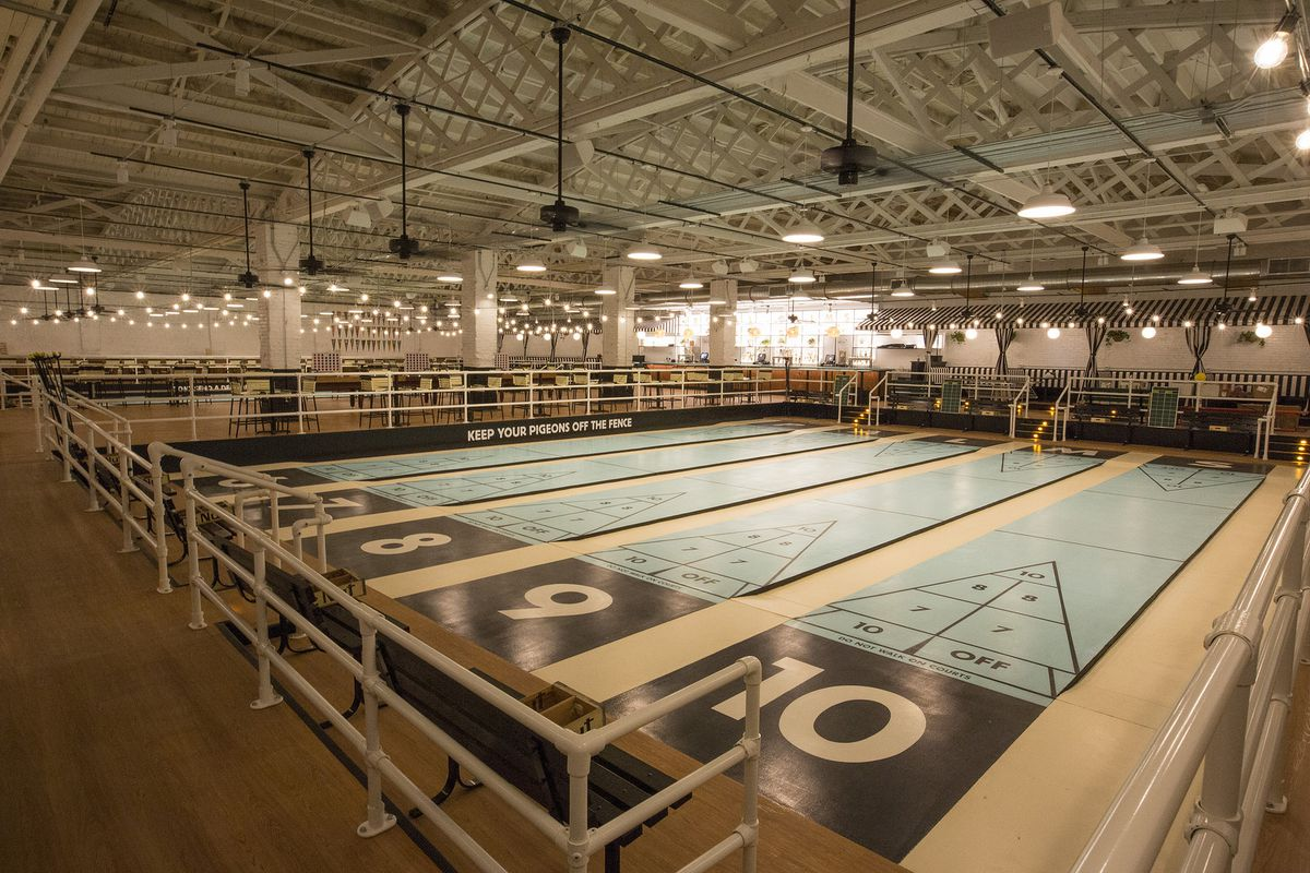 A glorious shuffleboard club with vacant lanes.